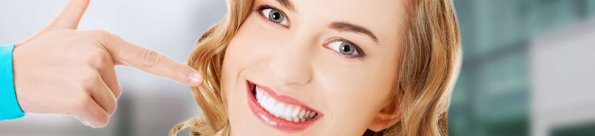 woman pointing at her nice teeth after dental cosmetic treatments