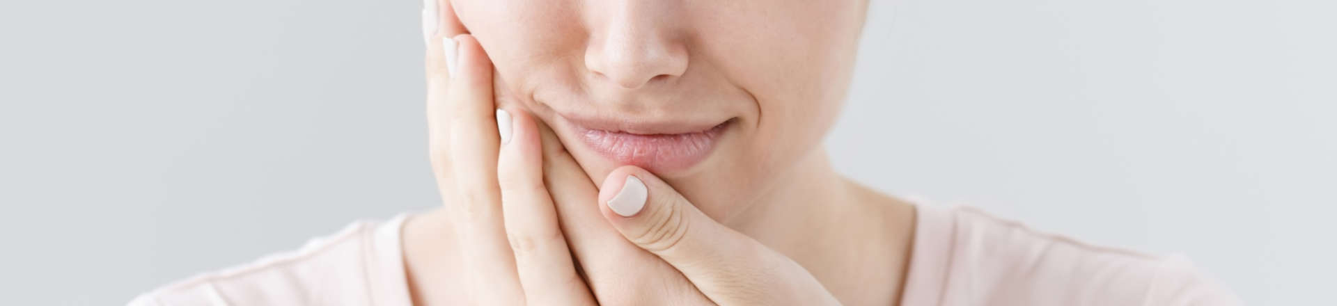 woman with dental pain pressing her cheek wth hands